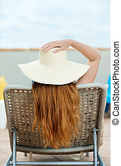 Redhead Woman In Straw Hat On Deck Chair - Rear view of a...