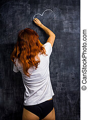 Redhead woman in underwear drawing on a blackboard