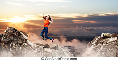 Redhead woman jumps over cliff on blue sky background.