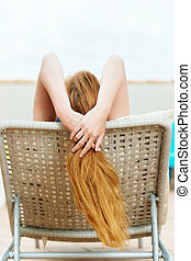 Redhead Woman Lies On Deck Chair - Rear view of a redhead...