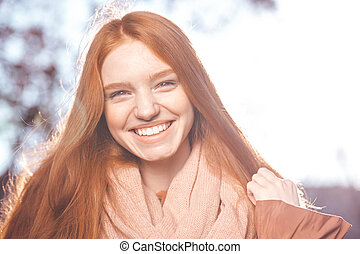 Redhead woman looking at camera outdoors