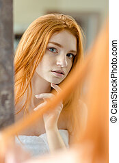 Redhead woman looking at her reflection in mirror