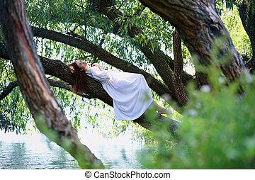 Redhead woman lying on a tree