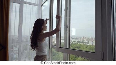 Redhead woman opens window and enjoys fresh air in her day...