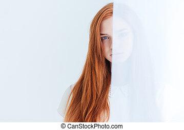Redhead woman peeking from curtain - Charming redhead woman...