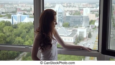 Redhead woman stands near open window and enjoys fresh air...