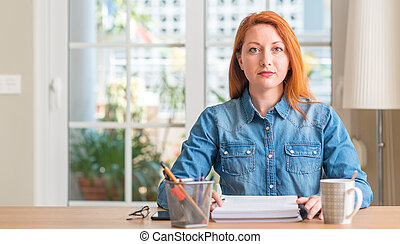 Redhead woman studying at home with a confident expression on smart face thinking serious