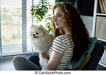 Redhead woman with a dog in the living room