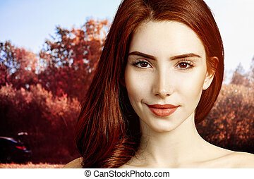 Redhead woman with perfect skin over autumn park background.