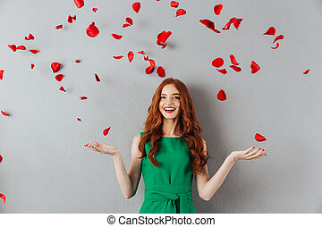 Redhead young happy lady over petals of roses