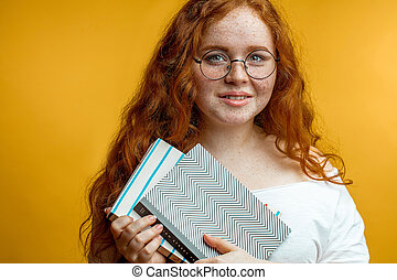 Redhead young woman holding blank books looking at the camera isolated yellow