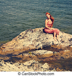 redhead young woman in a dress on the ocean coast
