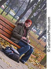 Redheaded girl in an autumn park