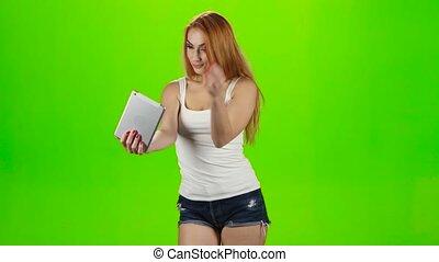 Redheaded girl model makes selfie on the tablet. Green screen