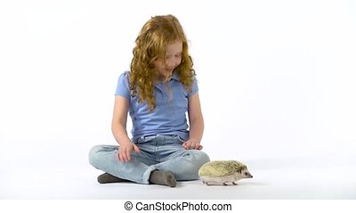 Redheaded little girl with curly hair is holding hedgehog at white background. Girl in blue T-shirt and jeans. Curious hedgehog is sniffing at studio. Slow motion