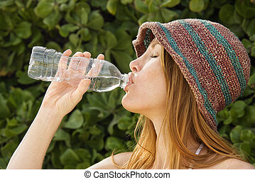 Redheaded woman drinking water.