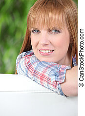 Redheaded woman leaning on the back of a white sofa