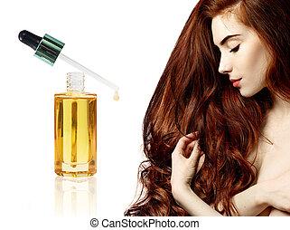 Redheaded woman near goldden bottle with oil.