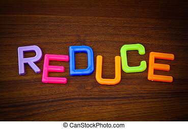Reduce in colorful toy letters on wood background