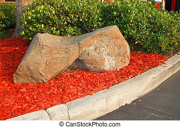 Redwood Mulch - Redwood mulch next to the rocks on a sunny...