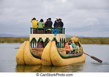 People are sitting in reed boat at lake Titicaca.