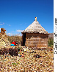 Hut made of reed and lots of drying reed on one of the floating Uros islands inside Lake Titicaca, Peru. The Uros islands are made of reed and they float on top of the lake.