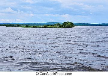 small reed island in the middle of a wide lake