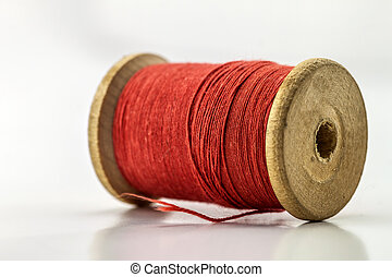 Reel or spool of red sewing thread isolated on white. Shallow depth of field. Close-up macro shot.