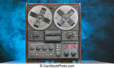 Reel to reel tape recorder playing against a smoky studio background with blue neon lights. Rotating vintage music player. Party. Front view. Popular disco trends 70s, 80s. Slow motion