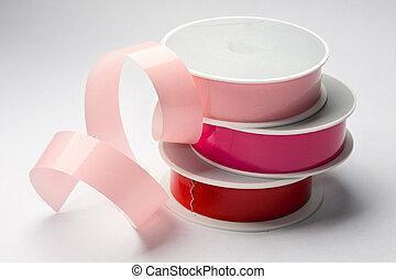 Reels of ribbon isolated on the grey background