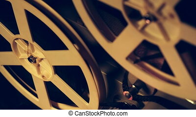 Reels with film rotating close up view. Vintage objects, cinematograph concept. Retro film projector playing in the dark room. Old-fashioned antique super 8mm film projector