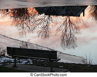 frozen pond with a bench and a house refection on the water