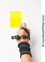Referee hand and whistle show Yellow card to player with ...