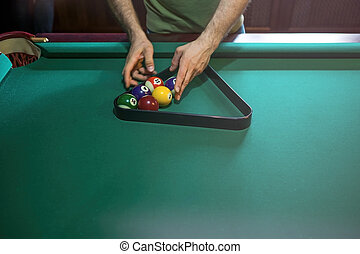 referee preparing the billiard balls on pool table
