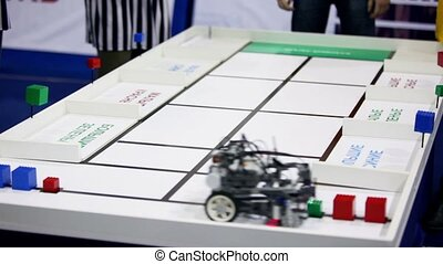Referee watch on robot moves, collects cubes and put them to...