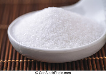 refined white sugar in a bowl on background