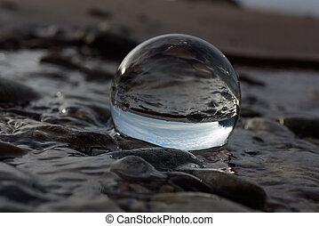 Reflect in crystal ball - Seashore is reflected inside the...