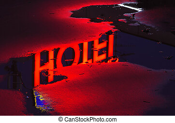Reflecting red neon light of a hotel - The red neon light of...