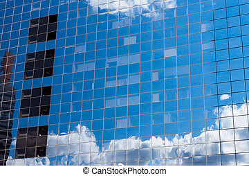 reflecting sky in glass of office building
