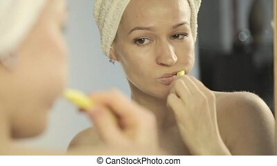 reflection in a mirror of beautiful woman with towel on a head brushing her teeth in bathroom