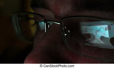 Reflection in glasses of stock market trade information from screen of tablet.