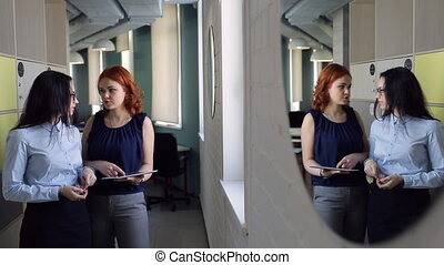 Reflection in mirror of two women discussing topics inside office.