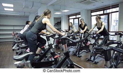 Reflection in mirror three women on stationary bike in gym