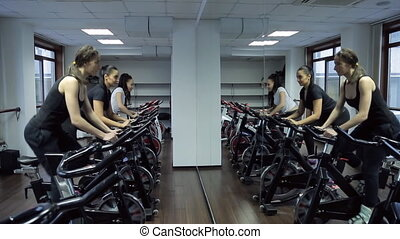 Reflection in mirror women doing exercise on stationary bike in gym
