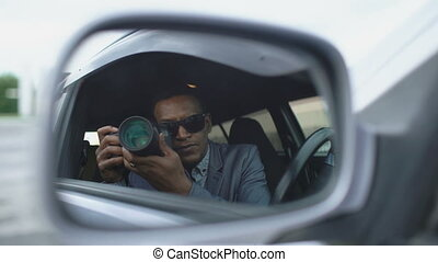 Reflection in side mirror of Paparazzi man sitting inside ...