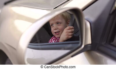 Reflection in the car mirror of a little boy who sits behind the wheel of a car.