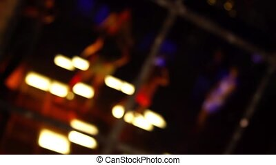 Reflection in the mirror dance floor in a disco club with young women dancing with defocused background