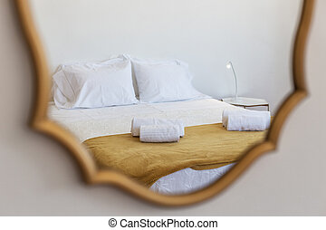 Reflection in the mirror of a bed with pillows, in the bedroom.
