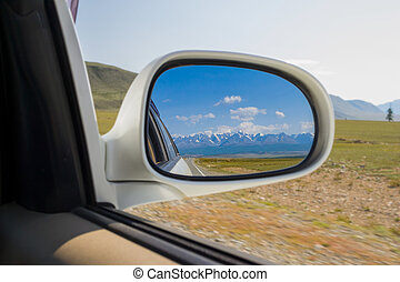 Reflection in the mirror of a riding white car of large altai mountains with snow on top by a sunny bright day with a blue clear sky green field and clouds