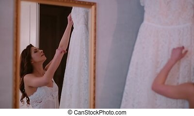 Reflection in the mirror. Young woman takes off a wedding dress from a hanger. Morning preparing to ceremony.
